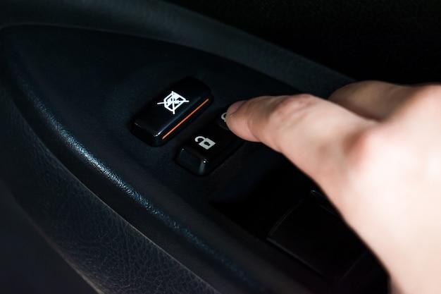 Close-up, mãos asiáticas, pressionando o botão para trancar a porta do carro dentro