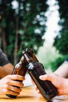 Close-up mãos, clinking, a, garrafas cerveja, sobre, a, tabela