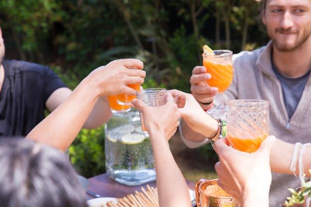 Close-up mãos, clinking, óculos, com, suco laranja