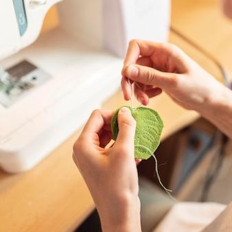 Close-up mãos costurando folha com agulha