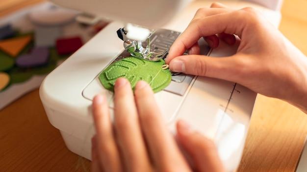 Close-up mãos costurando folha