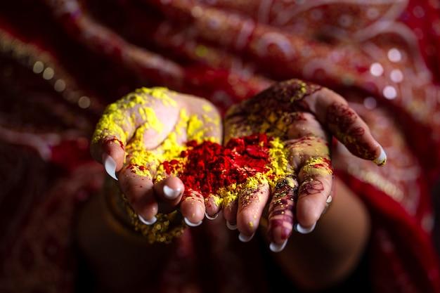 Close-up mãos da menina da índia segurando o pó colorido nas mãos no festival de holi