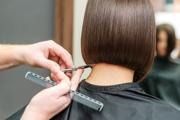 Close-up mãos de cabeleireiro profissional estão fazendo cabelo curto com tesoura e pente