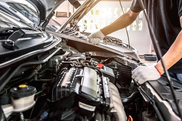 Close-up mãos de mecânico de automóveis usando a chave inglesa para manutenção do motor do carro.
