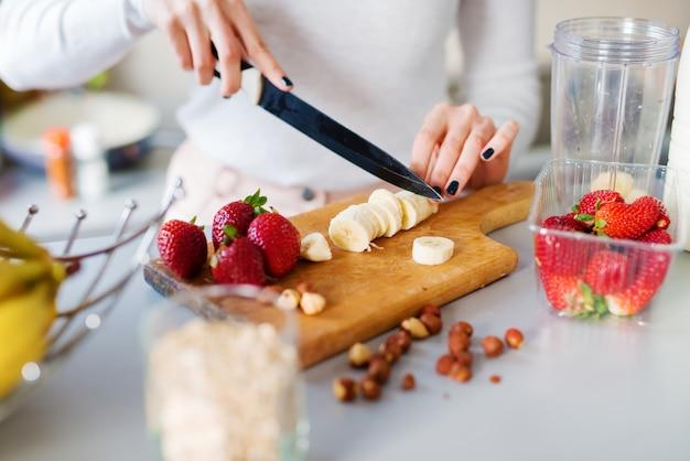 Close-up mãos de menina bonita estão cortando bananas e morangos no balcão da cozinha, preparando-os para um smoothie.