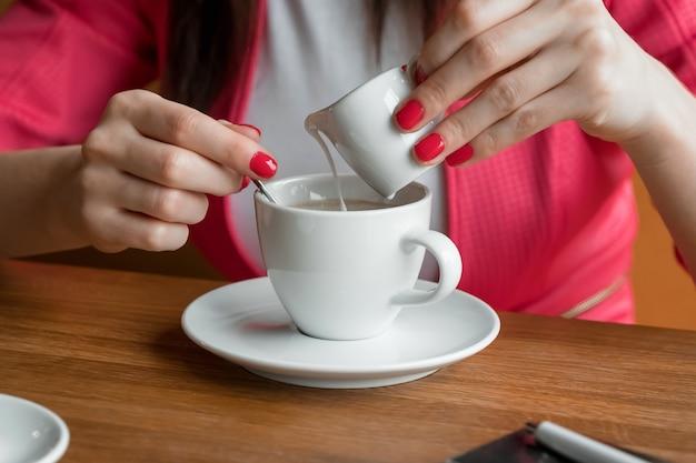 Close-up, mãos de uma jovem garota, derrama creme ou leite no café em um café na mesa de madeira.