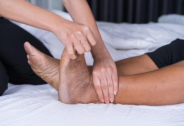 Close-up mãos fazendo massagem na velha mulher dor pernas na cama