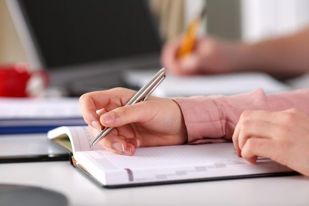 Close-up mãos femininas fazem uma entrada no diário