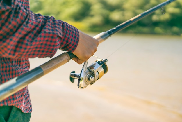 Close-up mãos masculinas pegando peixe com fiação na margem do rio.