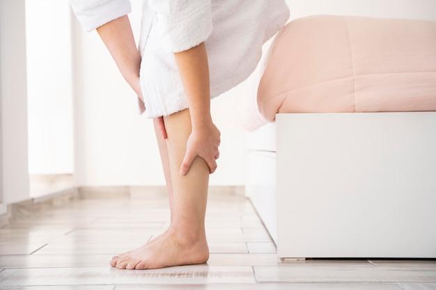 Close-up mãos massageando as pernas