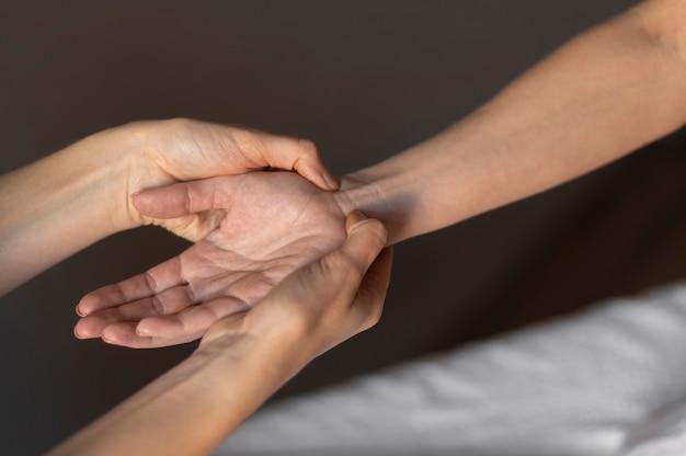 Close-up mãos massageando o pulso