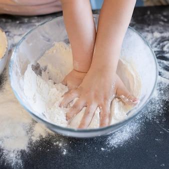 Close-up mãos pressionando farinha
