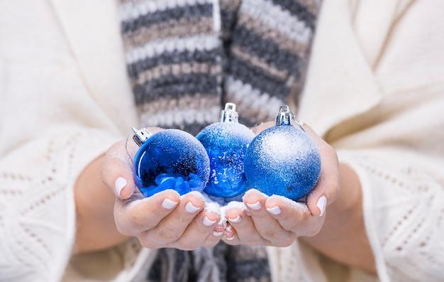 Close-up mãos segurando bolas de natal