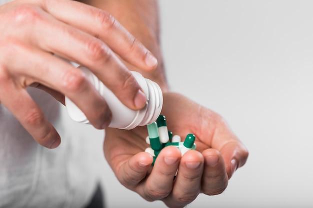 Close-up mãos segurando cápsulas coloridas