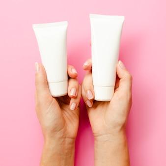 Close-up mãos segurando frascos de creme
