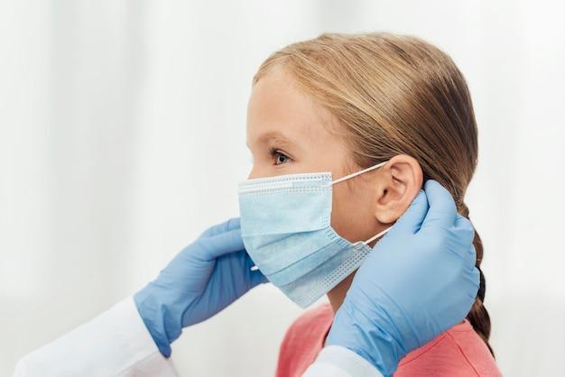 Close-up mãos segurando máscara médica
