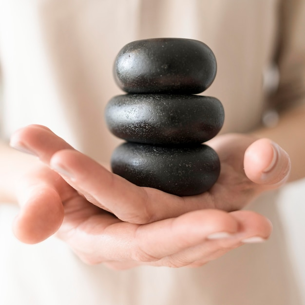 Close-up mãos segurando pedras spa