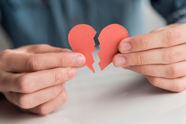 Close-up mãos segurando um coração partido