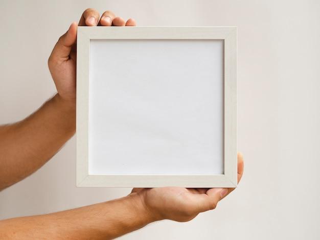 Close-up mãos segurando um modelo de quadro