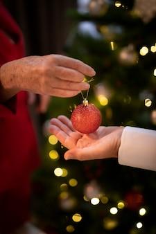 Close-up mãos segurando uma bola de natal