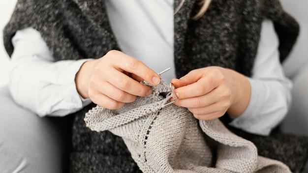 Close-up mãos tricotando manga