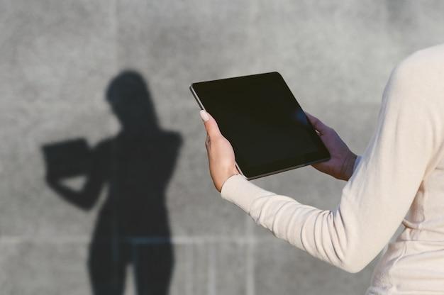 Close-up, maquete de um tablet nas mãos de uma menina. contra o fundo de uma parede de concreto cinza, uma silhueta permanece com uma sombra clara.