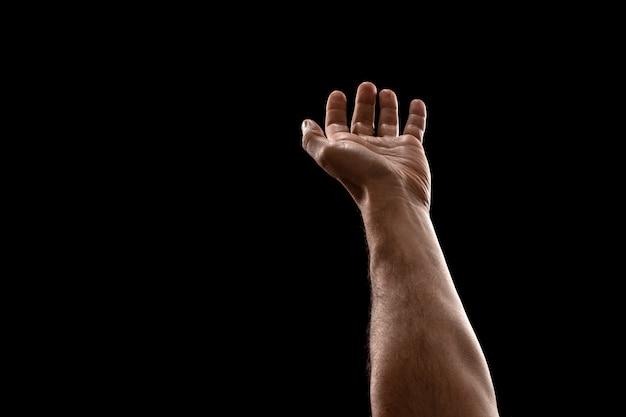 Close up masculino das mãos isolado no fundo preto.