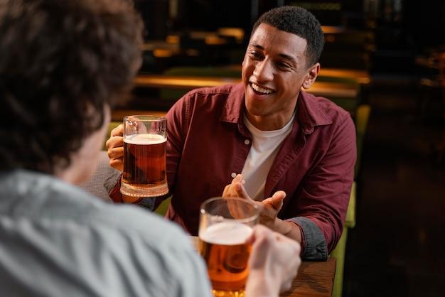 Close-up masculino em boteco com cerveja