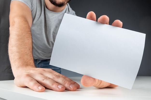 Close-up masculino mão segura um cartão branco, maquete, layout, cópia espaço fundo