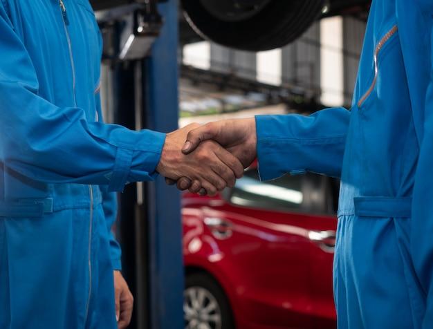 Close-up mecânico de automóveis, apertando as mãos na oficina de reparação automóvel