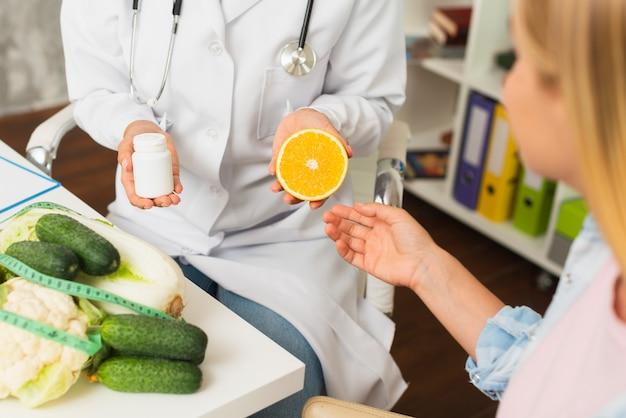 Close-up médico com recipiente de comprimidos e meia laranja