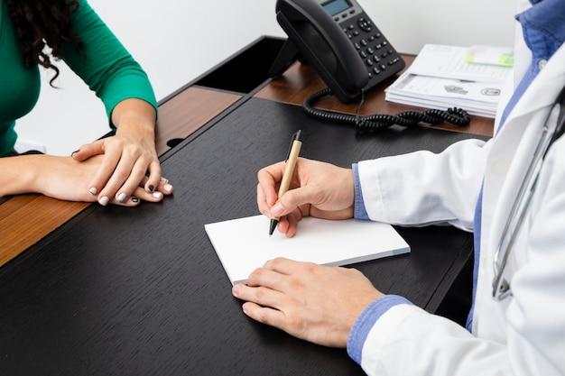 Close up médico escrevendo uma receita