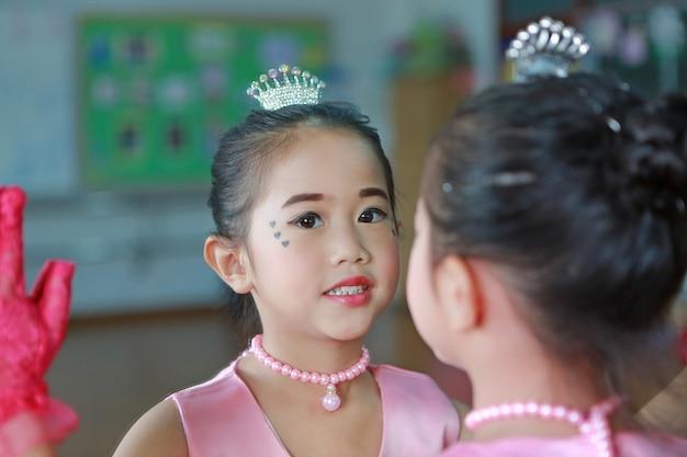 Close-up menina bailarina em um tutu rosa posando com reflexo do espelho