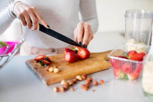 Close-up menina bonita é cortar morangos frescos no balcão da cozinha, preparando-os para serem misturados com bananas para um smoothie.