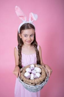 Close-up menina com orelhas de coelho da páscoa posando segurando uma cesta com ovos de páscoa festivos em uma parede rosa.