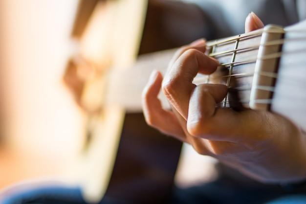 Close-up menina mão tocando guitarra