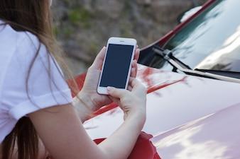 Close-up, menina, segurando, smartphone, capuz, car