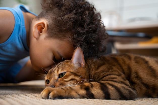 Close-up menino beijando gato