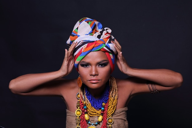 Close up metade do corpo de 20 anos mulher asiática com moda compõem o estilo tribo de colina africana. garota de pele bronzeada expressa sentimento forte, sorriso e feliz com acessórios étnicos coloridos sobre fundo preto