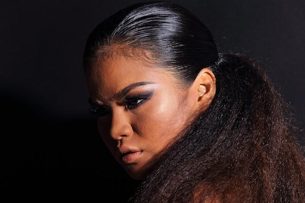 Close up metade do corpo de 20 anos mulher asiática com moda compõem o estilo tribo de colina africana. pele bronzeada garota cabelo alfro expressa sentimento forte, sorriso com acessórios étnicos coloridos sobre fundo preto