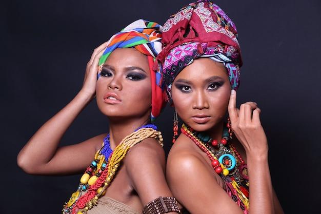 Close up metade do corpo dos anos 20 mulher asiática dois com moda compõem o estilo tribo de colina africana. meninas com pele bronzeada expressam sentimento forte, sorriso e felicidade com acessórios étnicos coloridos sobre fundo preto