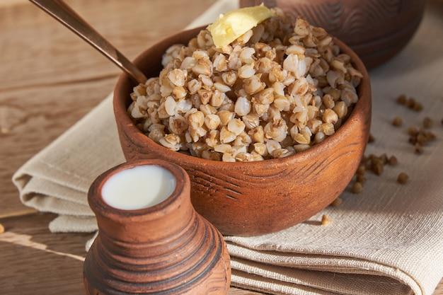 Close-up mingau de trigo sarraceno com manteiga em uma tigela em branco de madeira