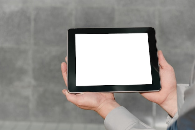 Close up, mock up tablet, apresentação do plano de negócios, mãos do homem. no contexto de uma parede de concreto.