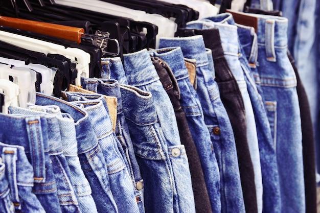 Close-up muitas calças de brim pendurado na prateleira