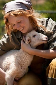 Close-up mulher abraçando um cordeiro