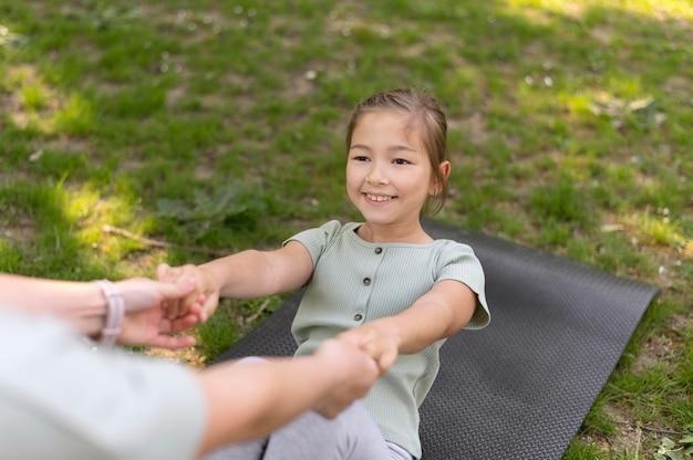 Close-up mulher ajudando menina a se exercitar