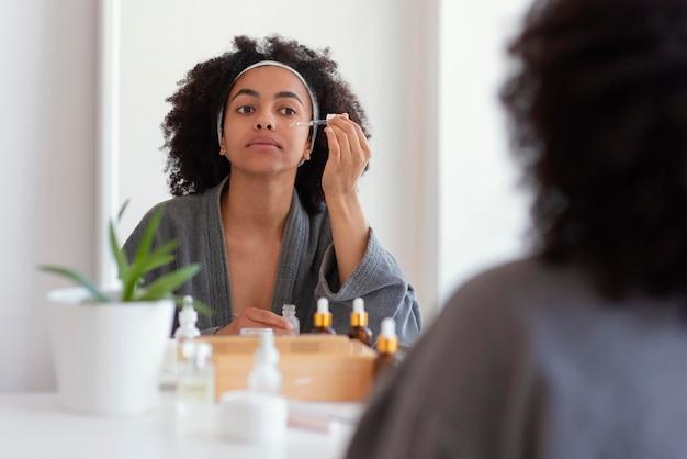 Close-up mulher aplicando soro