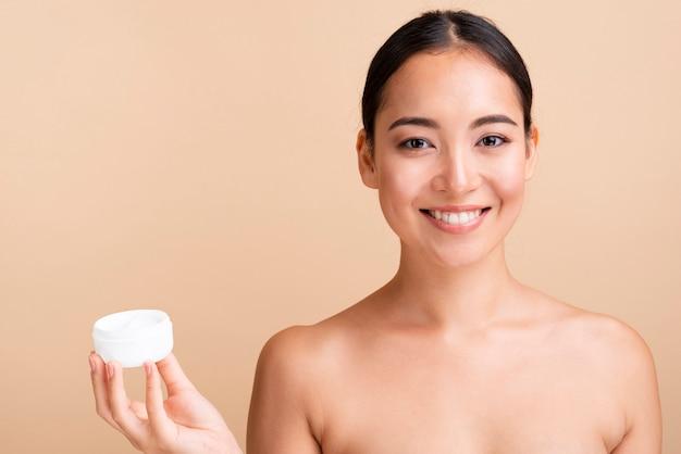 Close-up, mulher asiática, segurando, jarro creme