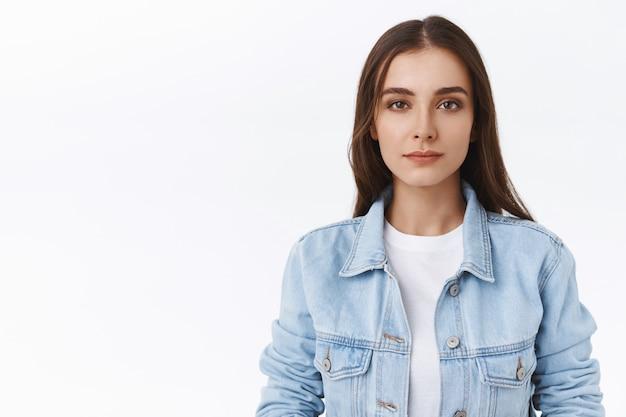 Close-up mulher caucasiana astuta e desconfiada, com os olhos semicerrados, olhar duvidoso, cético, descrente em suas palavras, indecisa e hesitante sobre um fundo branco, usar jaqueta jeans sobre camiseta