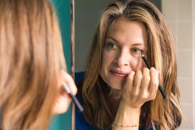 Close-up mulher colocando maquiagem